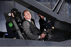 Defence Minister Peter McKay poses in an F-35 model. More serious: McKay's helicopter ride while search-and-rescue was being cut. Image source: CBC.